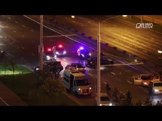 Десятки людей в форме бьют по машине