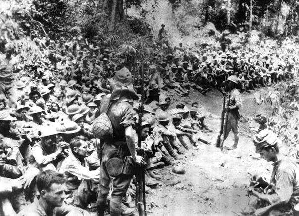 Японские солдаты охраняют американских военнопленных перед Батаанским маршем смерти в 1942 году Японцы заставили 75 тысяч американских и филиппинских военнопленных шагать в новый лагерь